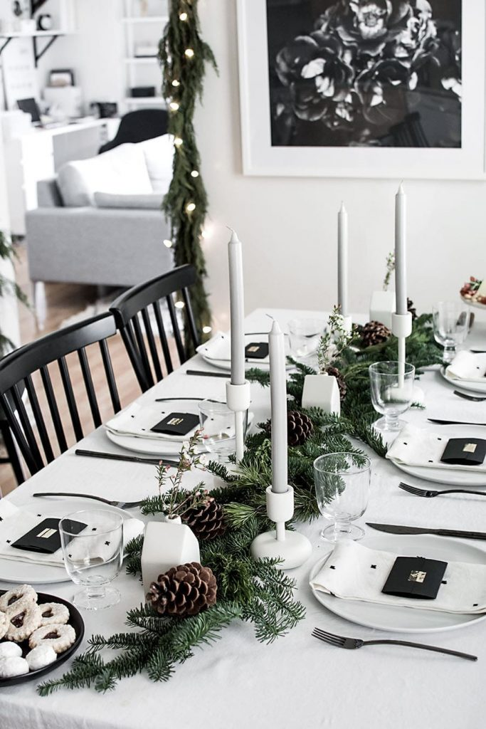 black and white christmas table decor with greenery runner and candles