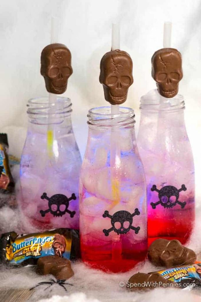 filled bottles of drink with skeleton straws
