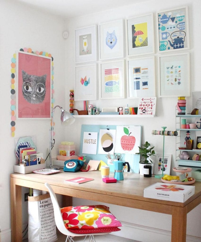 desk with lots of colourful prints in fun workspace
