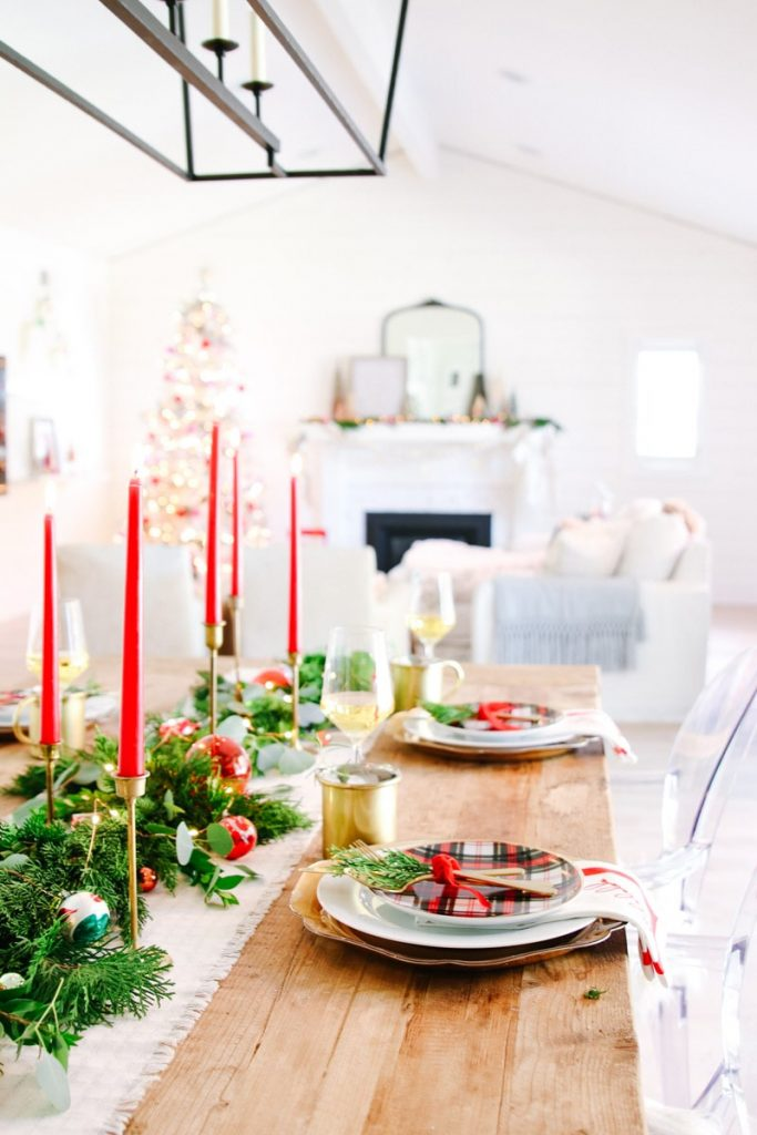 red and green christmas table with foliage runner and candles