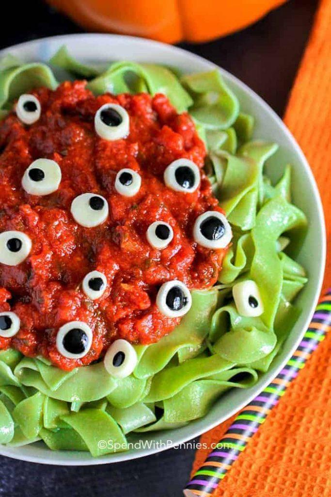 bowl of halloween green pasta, sauce and eyeballs