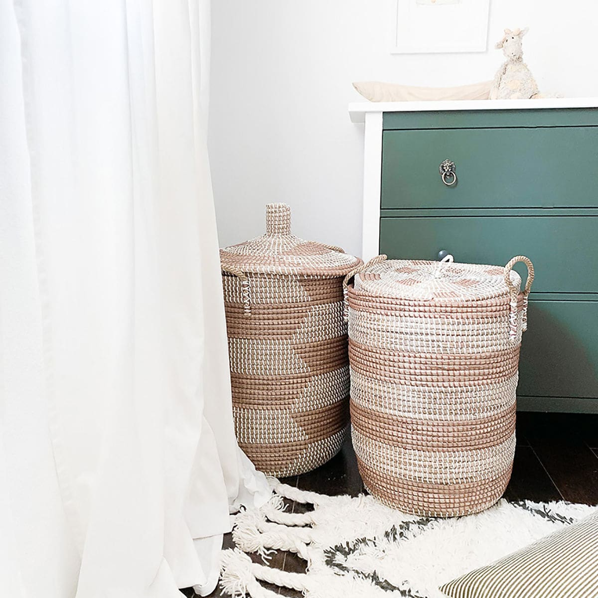 baby nursery with hampers, soft curtains, drawers and rug