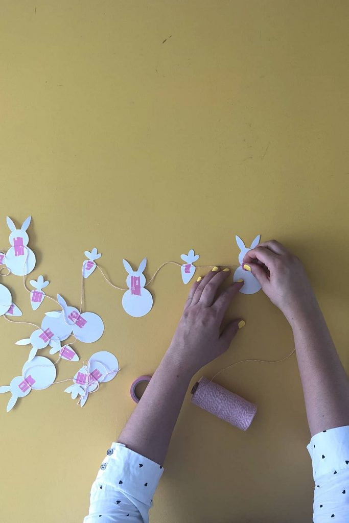 Hand placing tape on bunny shape to secure string