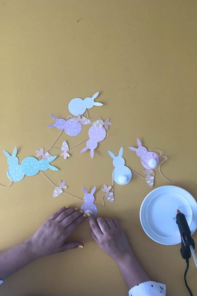 Sticking pom pom tail to paper bunny shape