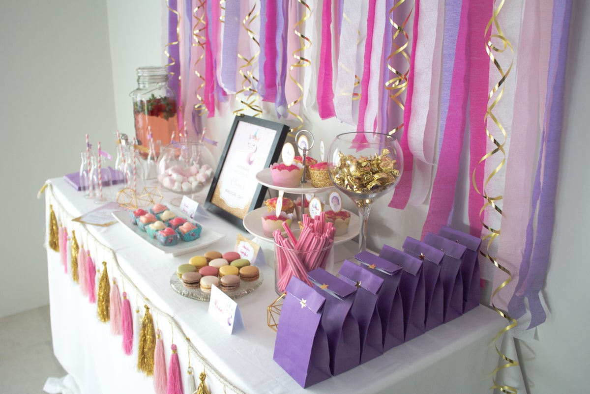 Unicorn party buffet with paper streamer backdrop