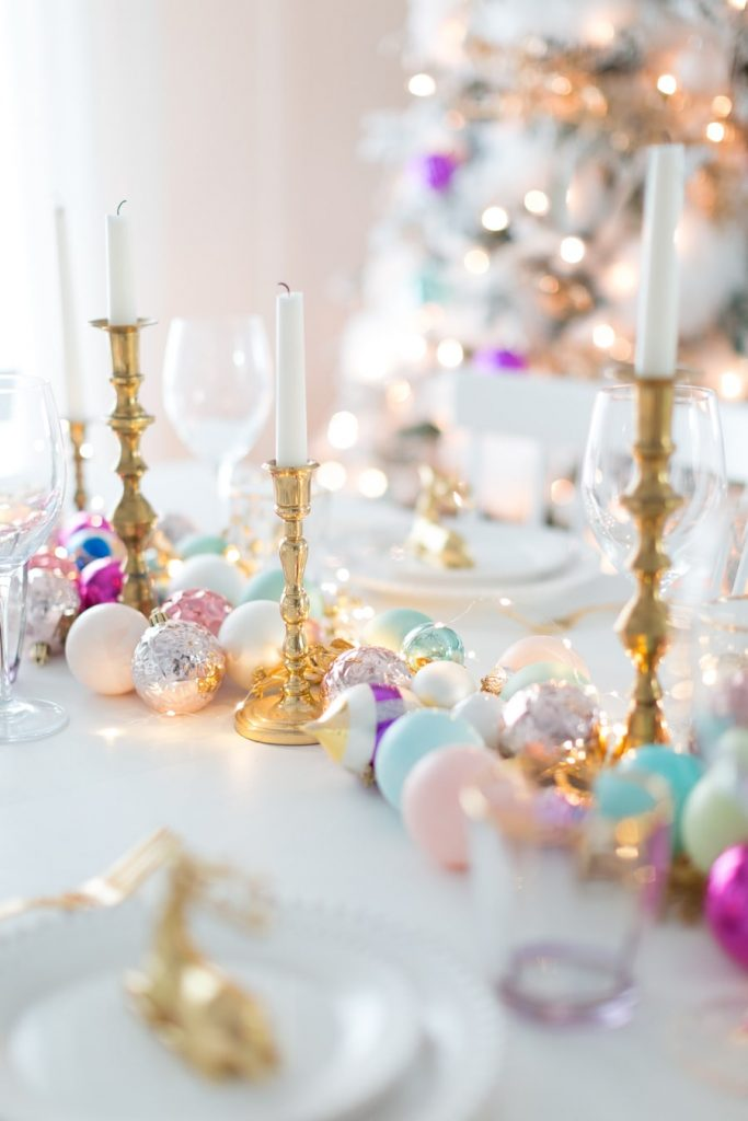 colourful baubles and candles on christmas table runner
