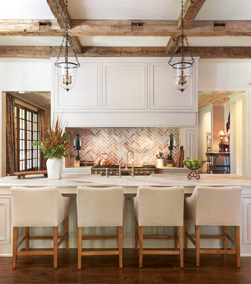 Casual formal farmhouse kitchen with timber beams, gold marble bench tops and herringbone brick back splash