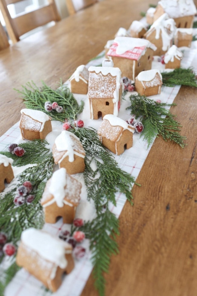 gingerbread houses on table runner with plants