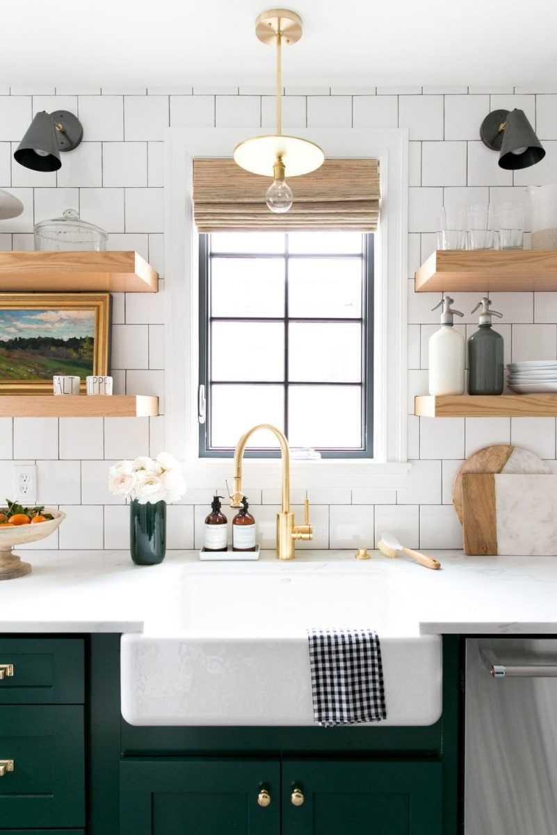 Green modern farmhouse kitchen with large sink, open shelving and gold fixtures