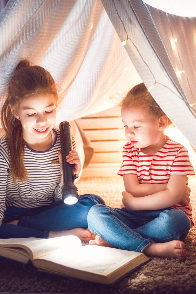 two girls reading book with flashlight under indoor tent