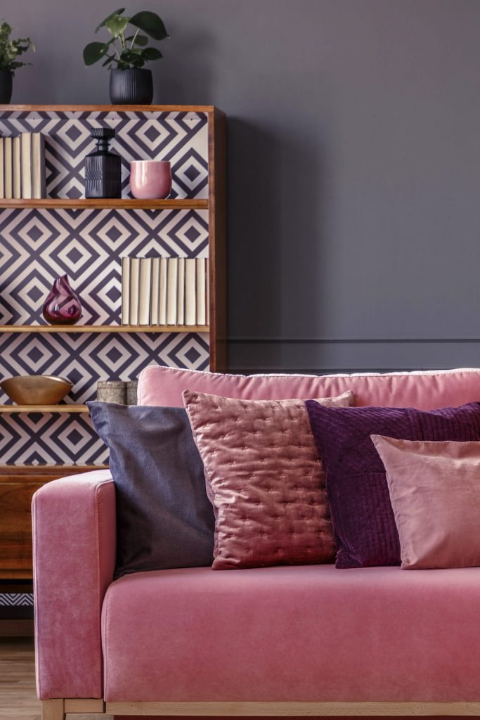 Pink couch and cushions with bookcase