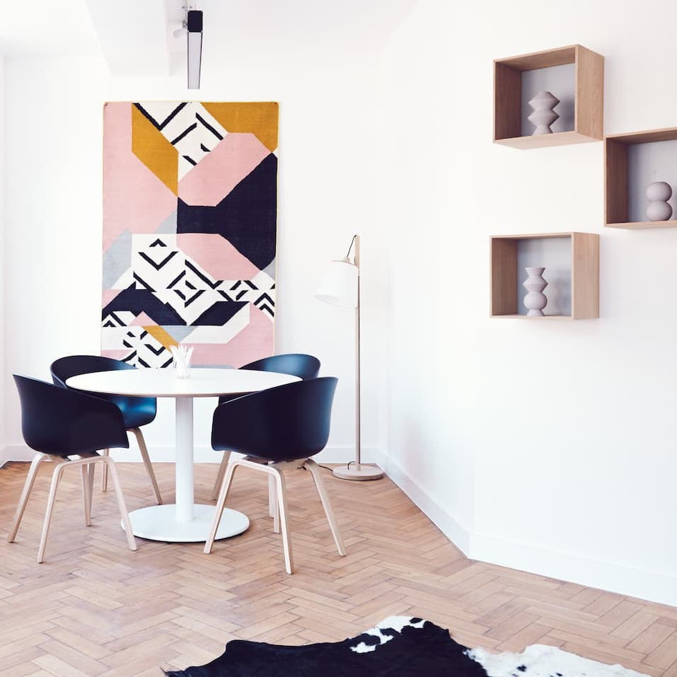 Sun filled dining room with colourful abstract art and decor cube shelving