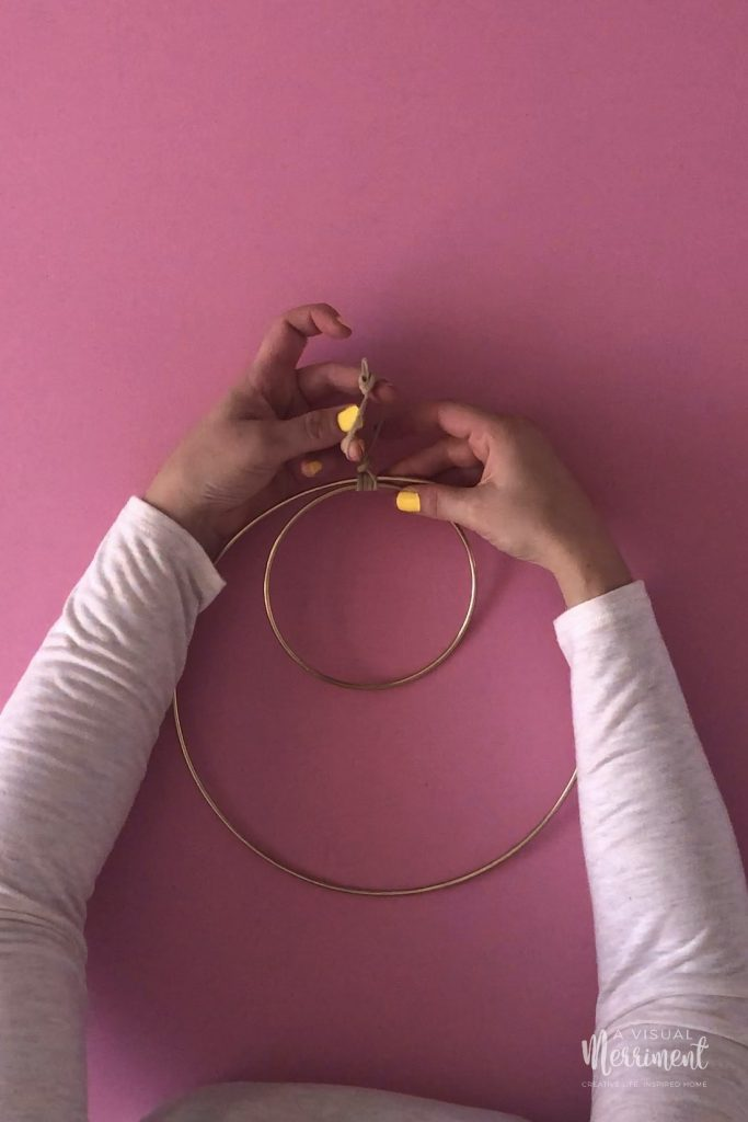 Holding fingers through wreath hanging loop