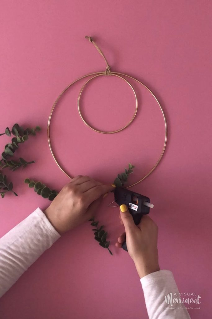 Using glue gun to attach branch to hoop