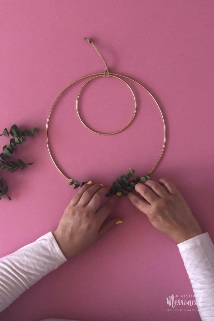 Sticking down leaf branches to wreath hoop