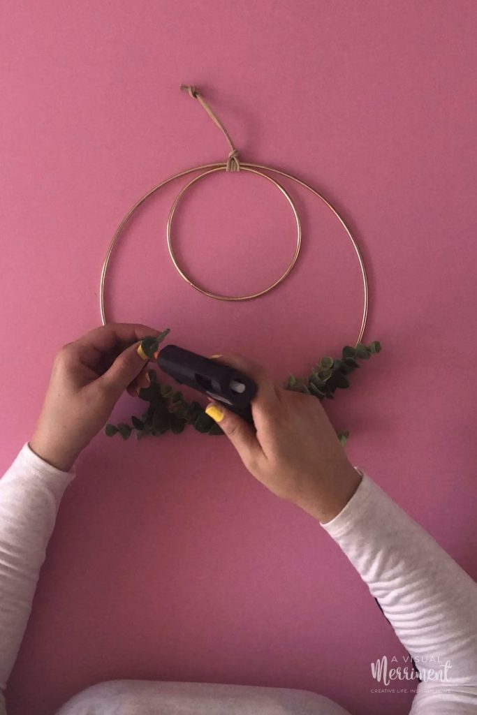 Adhering final leaf branch to hoop wreath