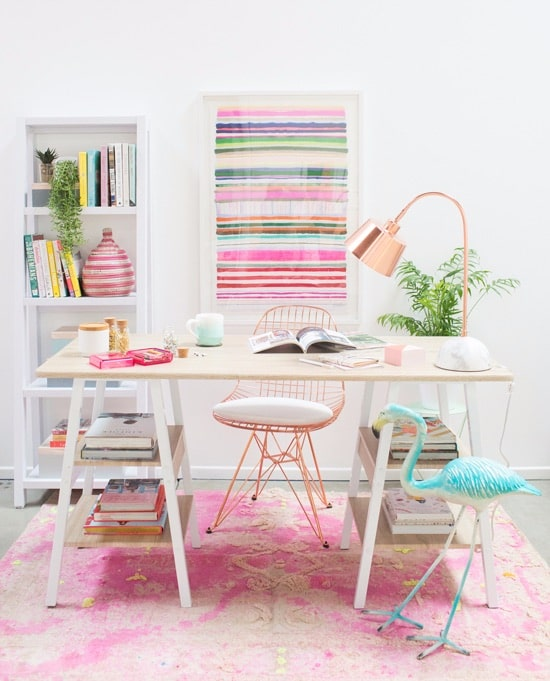 desk on pink rug with bright artwork