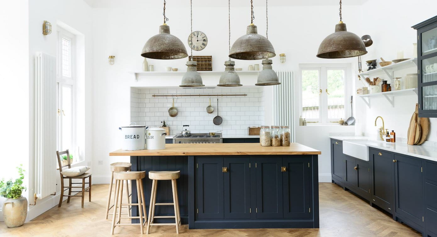 Blended old and new navy modern farmhouse kitchen with big old repurposed pendant lighting, island bench and open shelving
