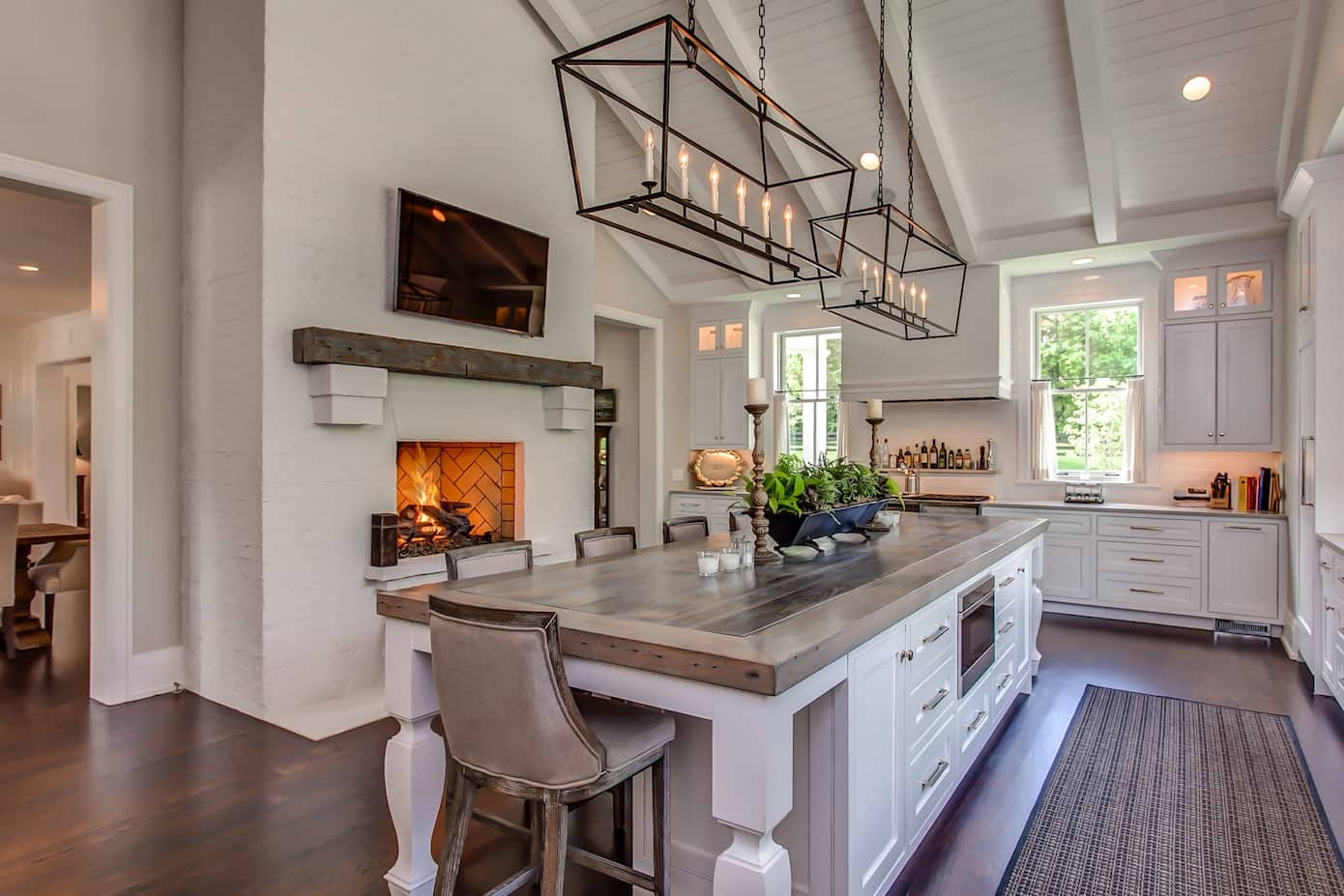 Modern farmhouse kitchen with raked high ceilings, fireplace and large island bench with industrial pendant lighting