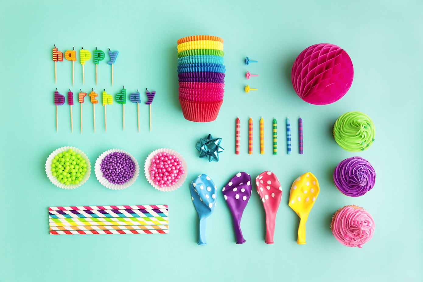 Colourful party balloons, decorations, candles, cupcakes, sprinkles flat-lay in bright colours