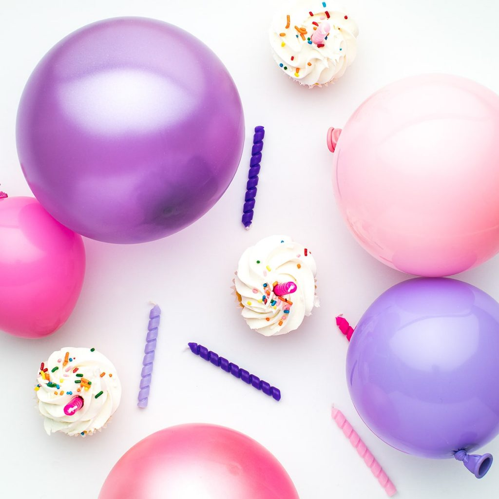 colourful balloons, candles and cupcakes for party