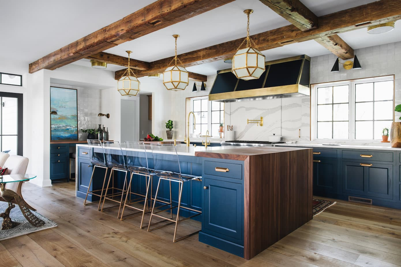 Modern farmhouse kitchen with timber beams, brass and gold accents and large kitchen island