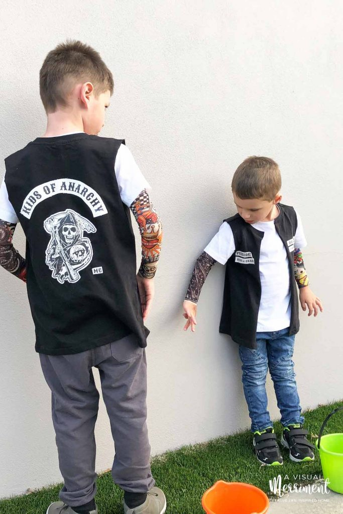 two boys standing against wall in biker costume