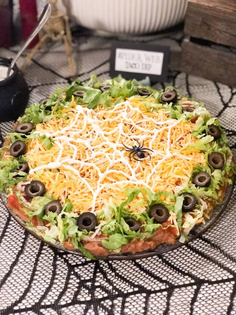 plate of taco dip with halloween decorated spider web