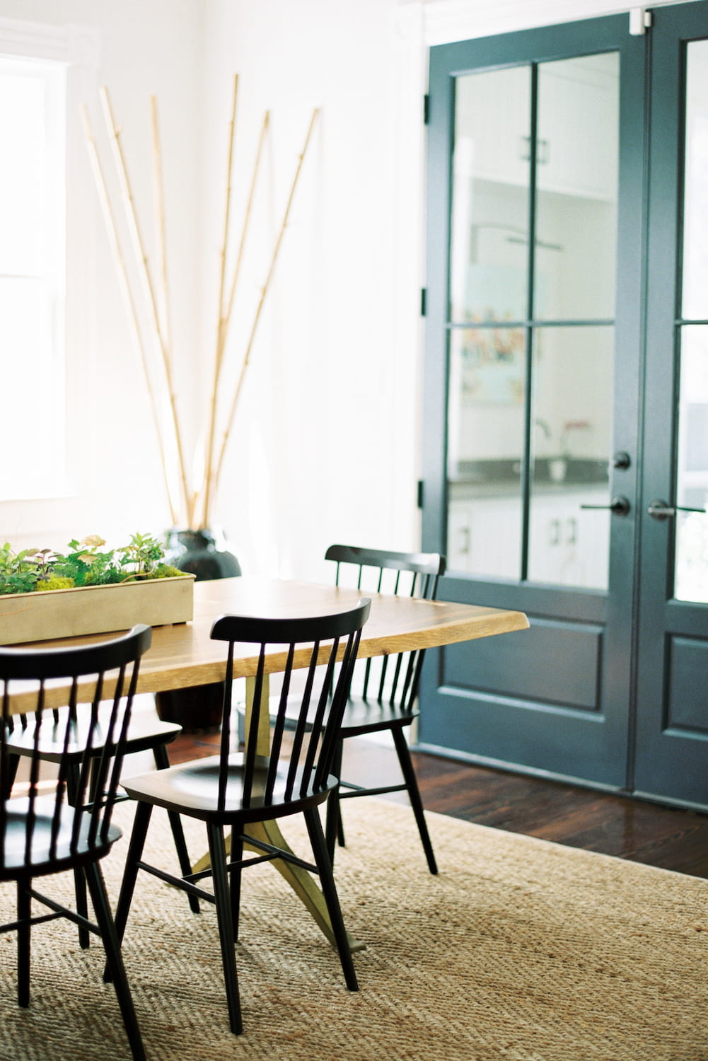 dining room with floor rug and green doors